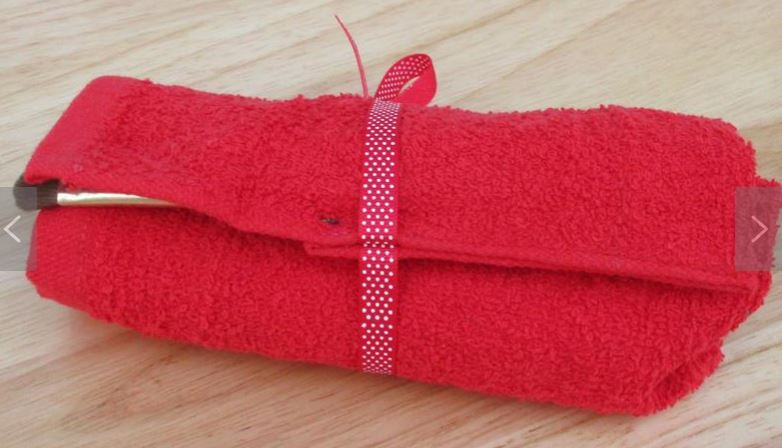Toothbrush travel pouch roll with red polka dot ribbon tied around the sanitary roll makeup brush