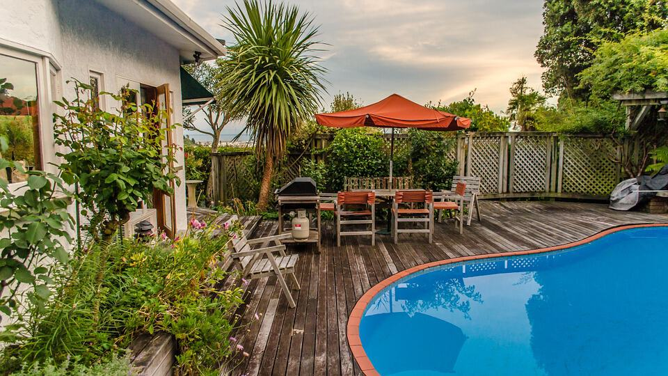 Backyard wow factor wooden fence deck swimming pool plants outdoor seating