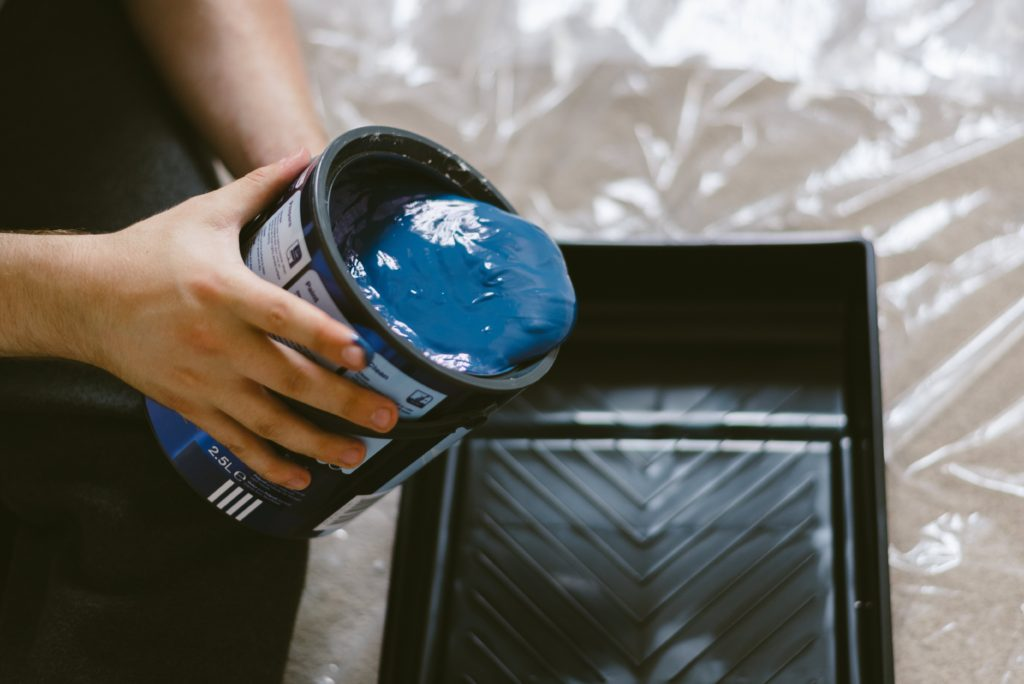 Sprce your home blue paint pouring into paint tray