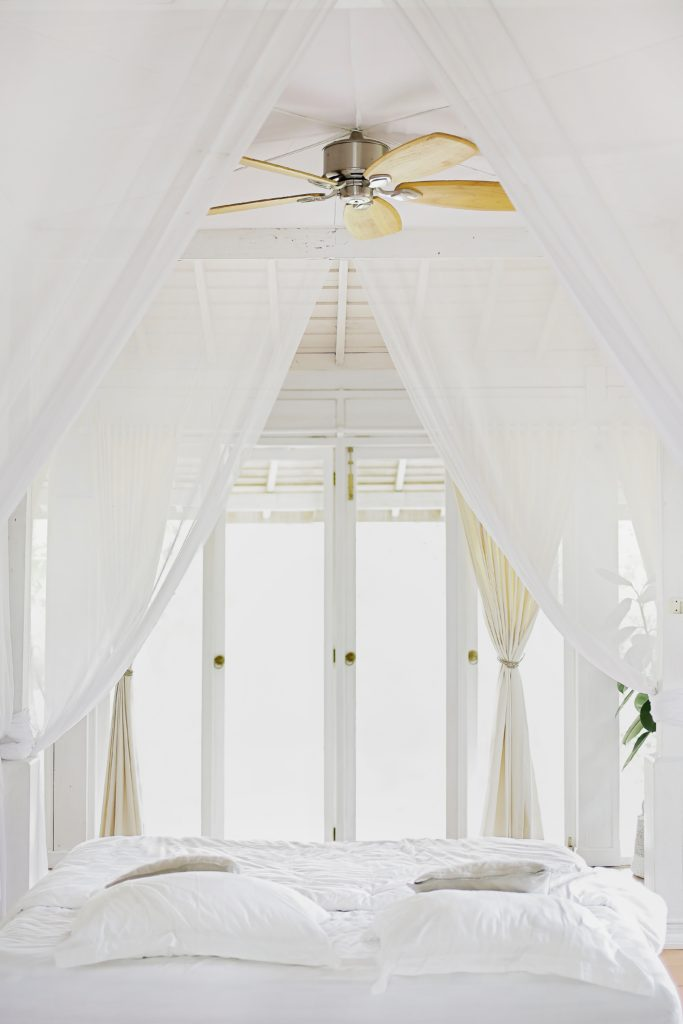 Bedroom designs ceiling fan over white duvet and pillows on a bed