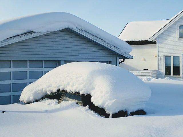 leaving winter behind at home car completely covered in snow in front of a garage